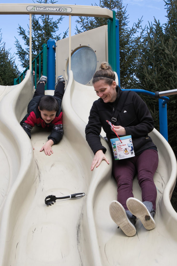 Student and teacher playing on slide