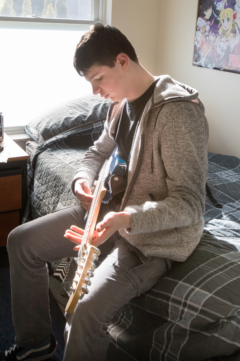 Residential student playing guitar